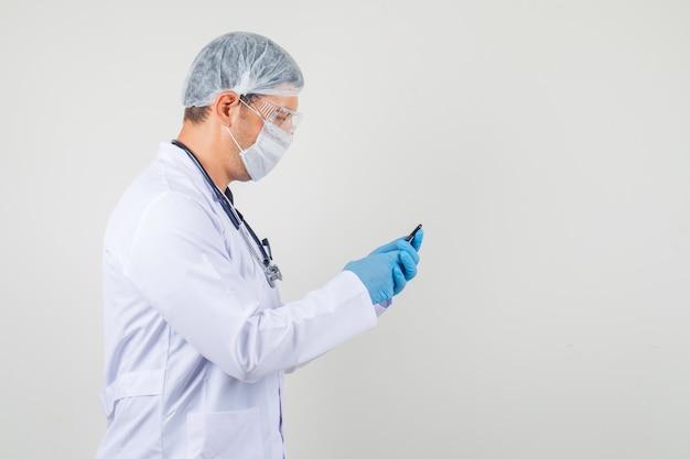Mannelijke arts die aan mobiele smartphone in beschermende kleding werkt