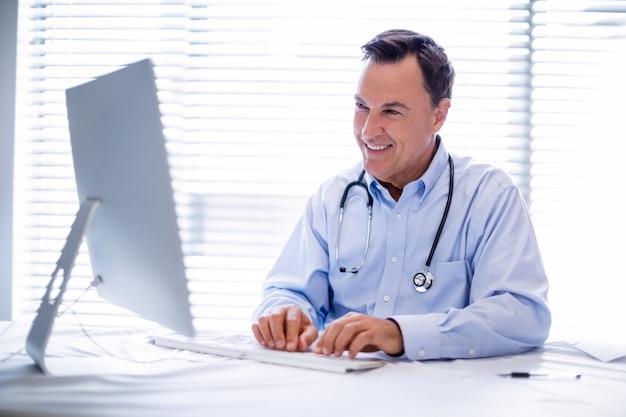Mannelijke arts die aan personal computer werkt