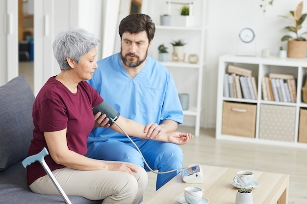 Mannelijke arts die bloeddruk van hogere vrouw meet terwijl zij op bank bij verpleeghuis zitten