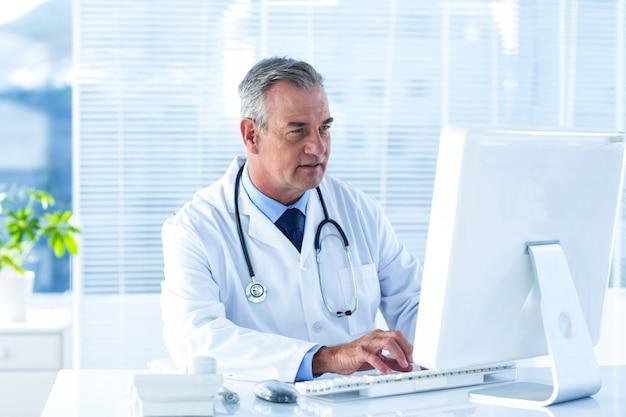 Mannelijke arts die computer in het ziekenhuis met behulp van