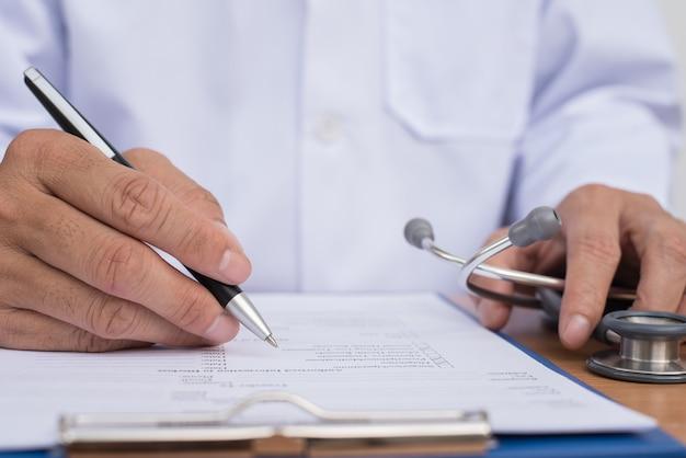 Mannelijke arts die de gezondheidschecklist van de patiënt of de geschiedenis van de patiënt van dichtbij vult