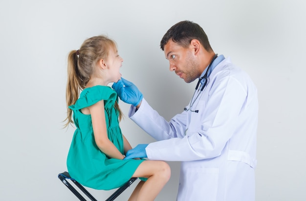 Mannelijke arts die de mond van het meisje in wit uniform, handschoenen onderzoekt