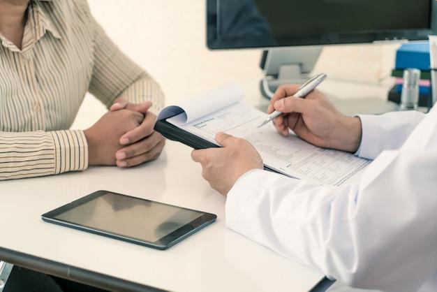Mannelijke arts die diagnose verklaart aan patiënt. vrouwenpatiënt die ongerust gemaakt kijken wanneer het luisteren bednieuws.
