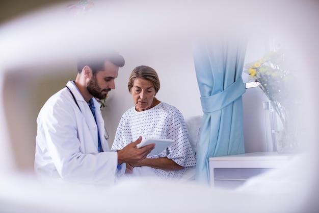 Mannelijke arts die digitale tablet tonen aan vrouwelijke hogere patiënt in de afdeling
