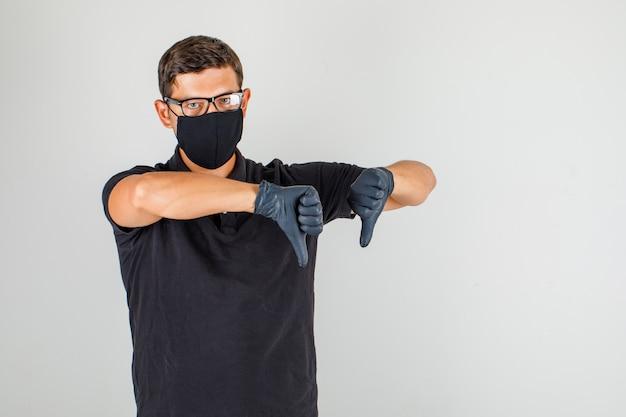 Mannelijke arts die duimen neer in zwart poloshirt tonen en ontevreden kijken