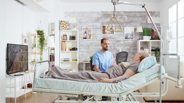 Mannelijke arts die een gesprek heeft met een zieke oude dame die in een ziekenhuisbed ligt in een verpleeghuis, medium shot.