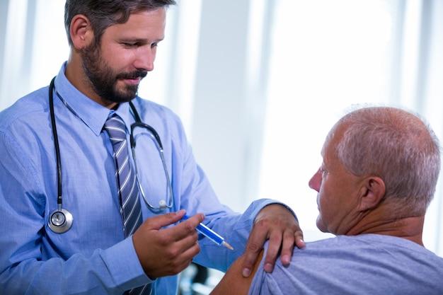Mannelijke arts die een injectie geeft aan een patiënt