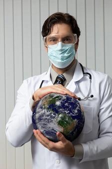 Mannelijke arts die een masker en een veiligheidsbril draagt met aarde in zijn handen, moe van het werken met covid-19 op een witte achtergrond.