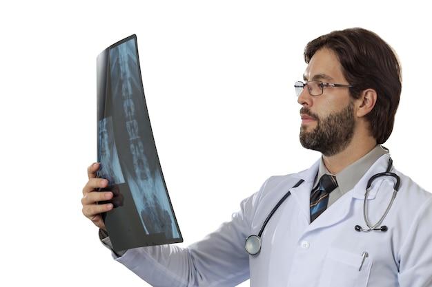 Mannelijke arts die een röntgenfoto op een witte ruimte bekijkt.