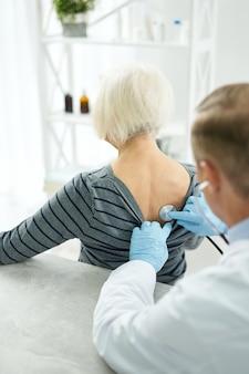 Mannelijke arts die een stethoscoop op de rug van een vrouwelijke patiënt zet en naar haar longen luistert