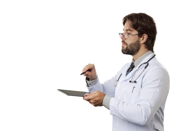 Mannelijke arts die een tablet op een witte ruimte bekijkt.