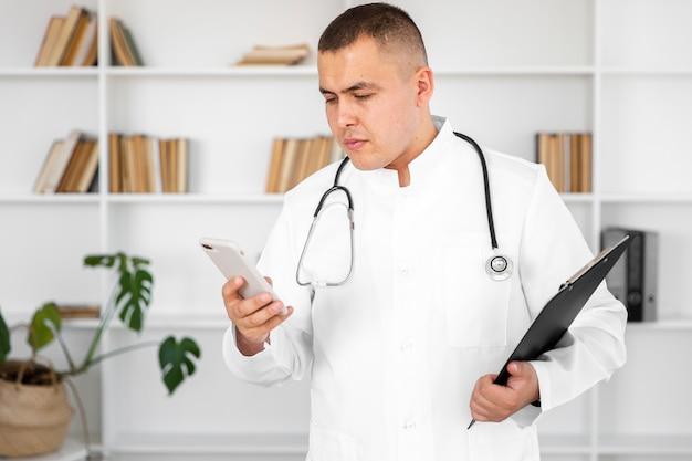 Mannelijke arts die een telefoon en een klembord houdt