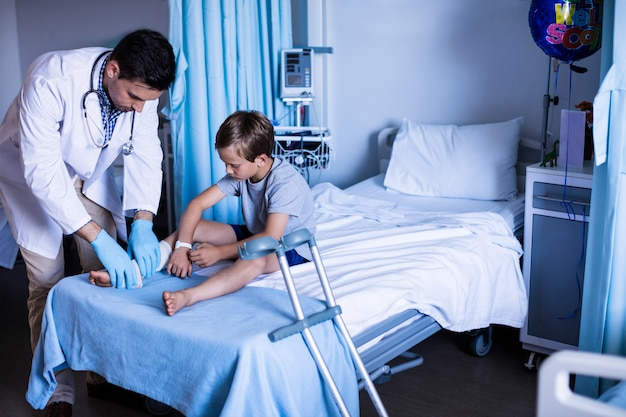 Mannelijke arts die geduldig been onderzoekt