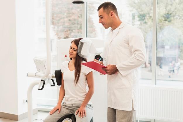 Mannelijke arts die geduldige voorwaarde op klembord schrijft