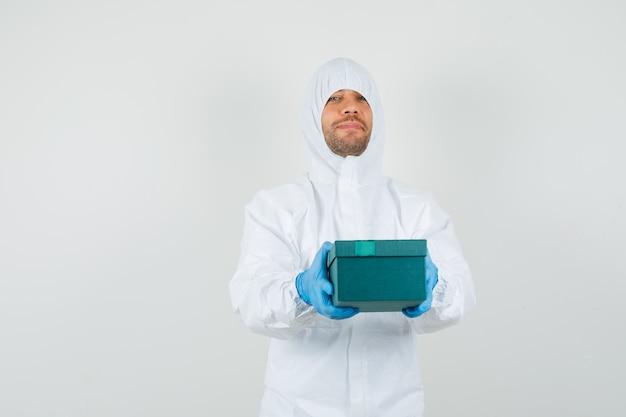 Mannelijke arts die giftdoos in beschermend kostuum voorstelt