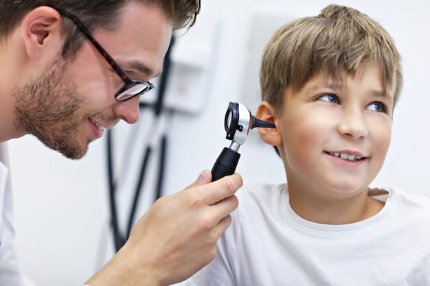 Mannelijke arts die het oor van de jongen onderzoekt met een otoscoop