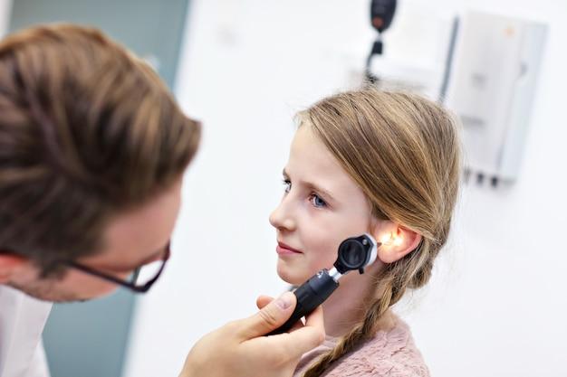 Mannelijke arts die het oor van het meisje onderzoekt met een otoscoop