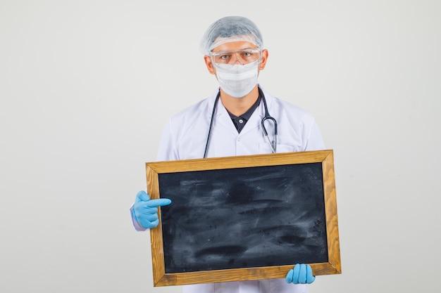 Mannelijke arts die leeg bord in beschermende kleren houden en zeker kijken.