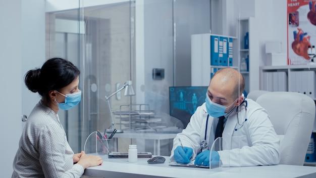 Mannelijke arts die medicijnen voorschrijft aan vrouwelijke patiënten tijdens de wereldwijde gezondheidscrisis van covid-19, ze praten door een plexiglazen muur en dragen maskers en handschoenen. medische consultatie in beschermingsmiddelen