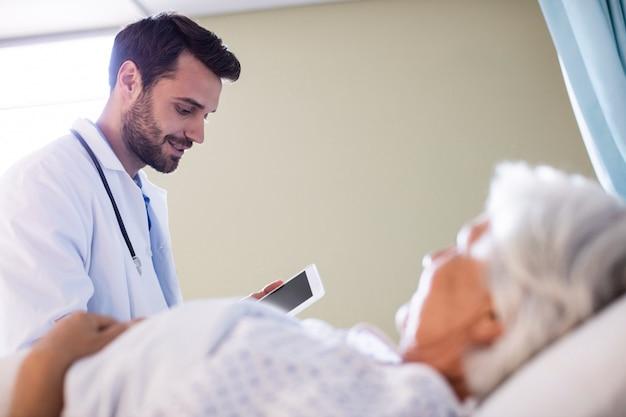 Mannelijke arts die medisch rapport over digitale tablet bespreken met vrouwelijke hogere patiënt in de afdeling