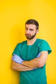 Mannelijke arts die met gekruiste wapens wenkbrauw opheft