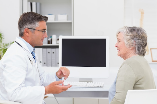 Mannelijke arts die met hogere patiënt bij lijst converseert