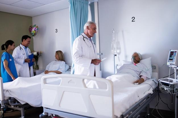 Mannelijke arts die met hogere patiënt op de afdeling interactie aangaan