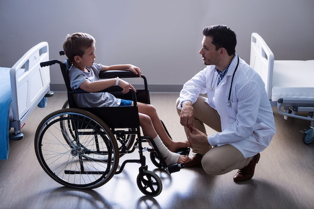 Mannelijke arts die met kindpatiënt interactie aangaan in afdeling
