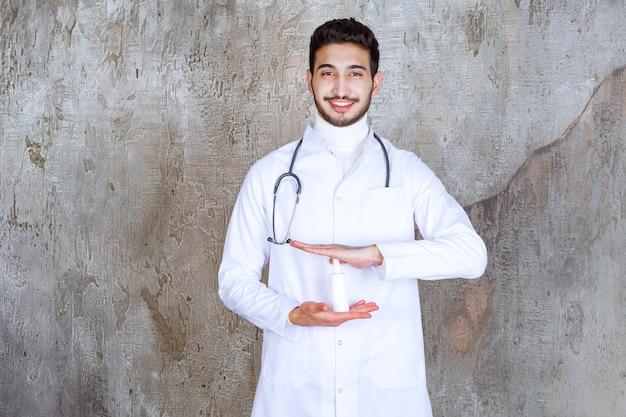 Mannelijke arts die met stethoscoop een witte fles met handdesinfecterend middel houdt.