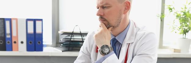 Mannelijke arts die op kantoor naar het scherm van de laptop kijkt