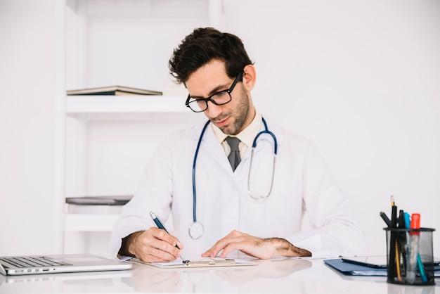Mannelijke arts die op klembord in het ziekenhuis schrijft