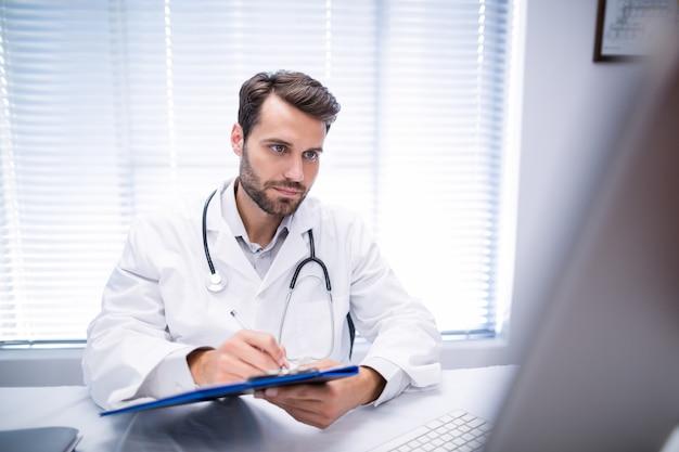 Mannelijke arts die op klembord schrijven terwijl het werken aan personal computer