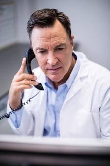 Mannelijke arts die op telefoon op elkaar inwerkt