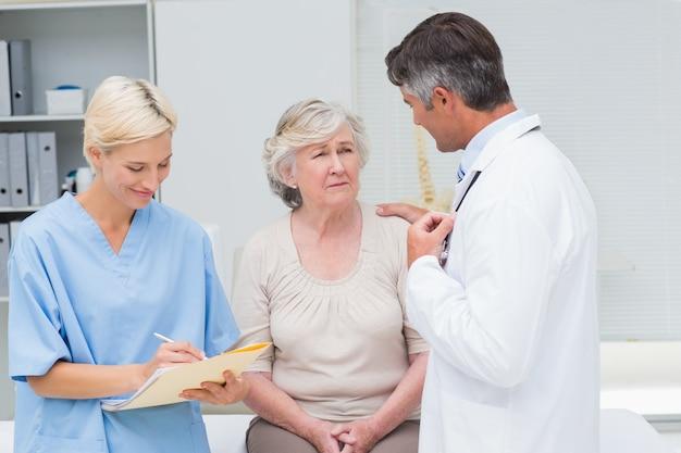 Mannelijke arts die patiënt troost terwijl verpleegster het schrijven rapporten in kliniek