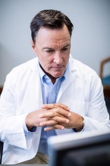 Mannelijke arts die personal computer bekijkt