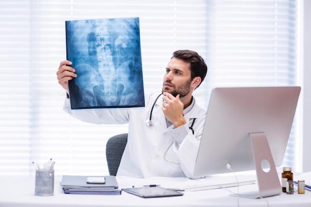 Mannelijke arts die röntgenstraal onderzoekt