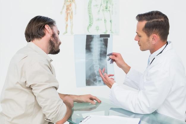 Mannelijke arts die stekelröntgenstraal verklaart aan patiënt