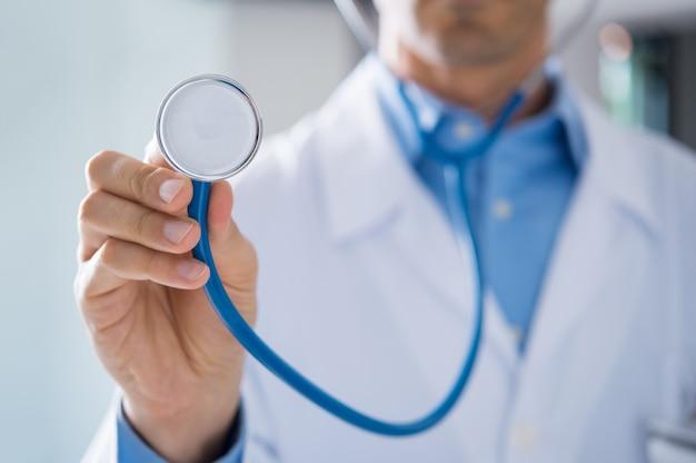 Mannelijke arts die stethoscoop toont voor controle