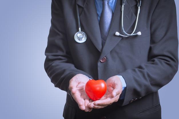 Mannelijke arts die stethoscoop voor controlehart toont, het concept van de hartzorg