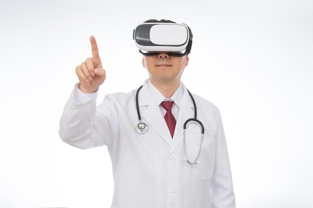 Mannelijke arts die virtual reality-bril draagt die op wit wordt geïsoleerd,
