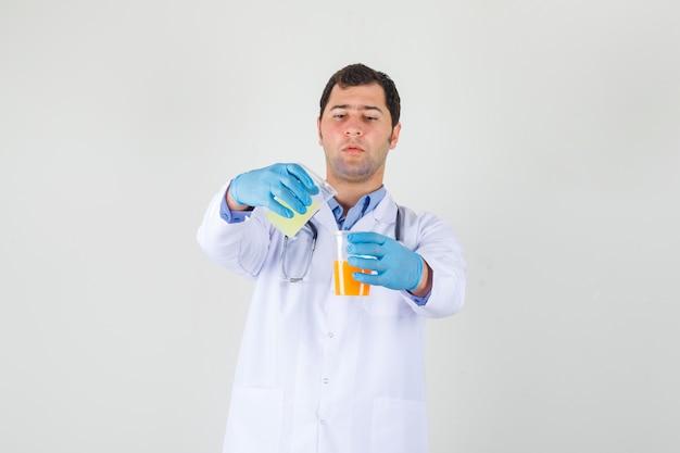 Mannelijke arts die vruchtensap mengt door in witte jas, handschoenen te gieten