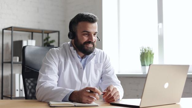 Mannelijke arts die witte jas draagt die patiënt online raadpleegt met behulp van hoofdtelefoon en webcamera op laptop.
