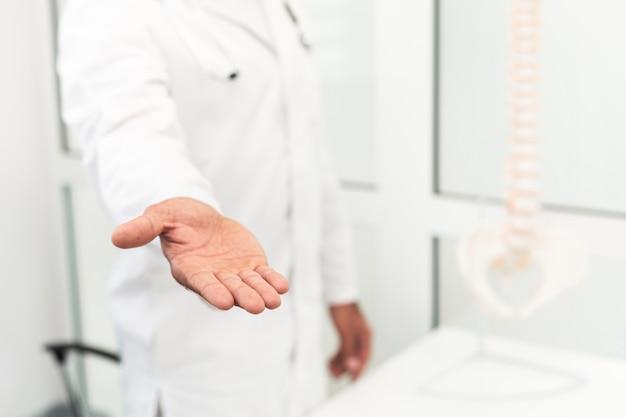 Mannelijke arts die zijn hand aanbiedt
