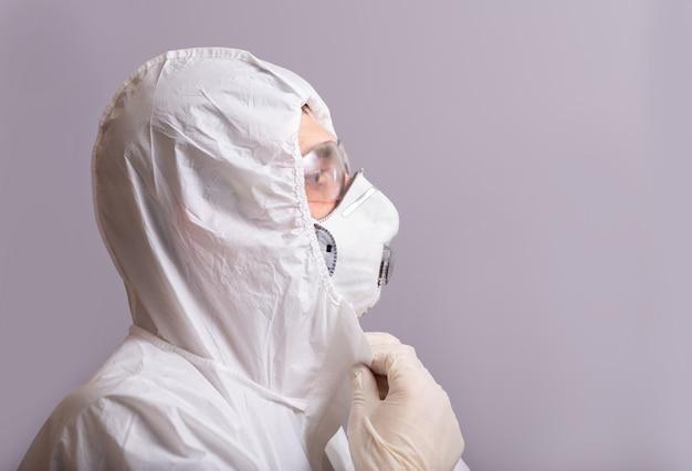 Mannelijke arts draagt een beschermend pak tegen bacteriële en virale infectie, covid 19, tijdens een pandemie, bril, masker ter bescherming, rubberen handschoenen. stop, blijf thuis.