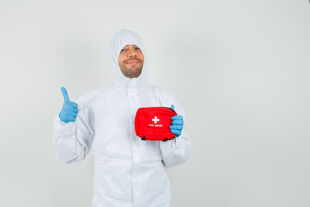 Mannelijke arts ehbo-kit houden, duim opdagen in beschermend pak