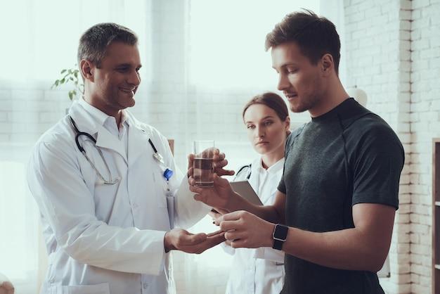 Mannelijke arts geeft pillen aan sportman