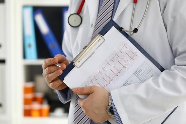 Mannelijke arts hand houdt zilveren pen vulling patiëntgeschiedenis lijst op klembord pad