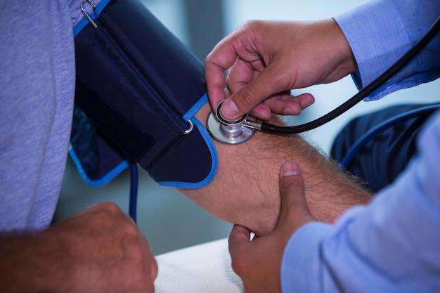 Mannelijke arts het controleren van de bloeddruk van de patiënt