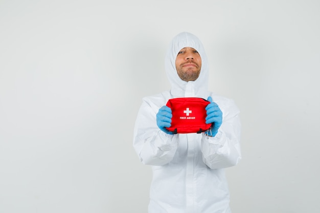 Mannelijke arts in beschermend pak, handschoenen die ehbo-doos houden en optimistisch kijken