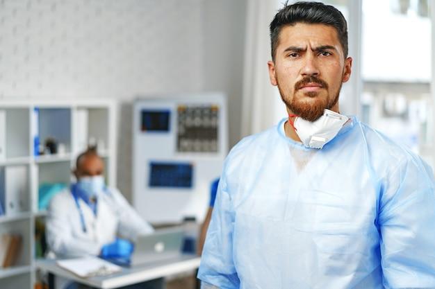 Mannelijke arts in beschermende medische jurk staande in ziekenhuiskast
